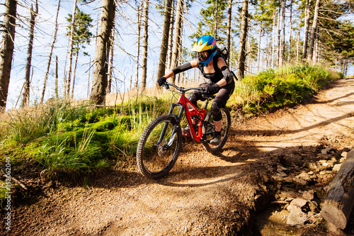 Stampa su Tela Picture of young woman riding mtb mountain bike, downhill