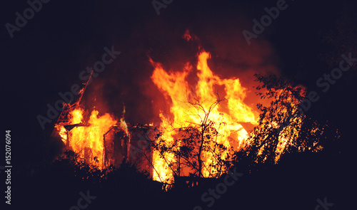 Photo Arson or nature disaster - burning fire flame on wooden house roof