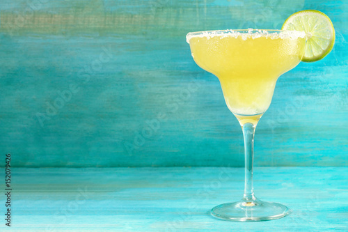 Photo sur Aluminium Cocktail Lemon Margarita cocktails on vibrant turquoise with copyspace