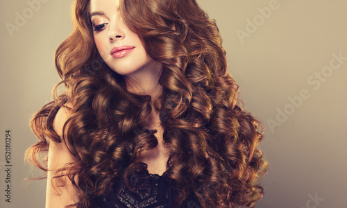 Cadres-photo bureau Salon de coiffure Brunette girl with long and shiny wavy hair . Beautiful model with curly hairstyle .