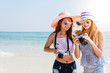 Two cool trendy hipster girls at the beach enjoying vacation on a tropical island, perfect tanned body, healthy skin, sexy stylish casual wear, bikini, blonde and brunette with the camera, sunglasses