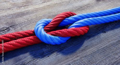 Photo Kreuzknoten mit rotem und blauem Seil auf Holz