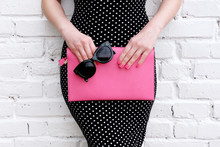 Fashion Woman In Dress Posing With Pink Leather Bag . Close Up