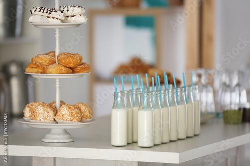 Foto op Aluminium Milkshake Table with bottles of milk and dessert stand