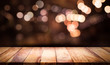 canvas print picture Wood table top with blur light bokeh in dark night cafe,restaurant background .Lifestyle and celebration concept