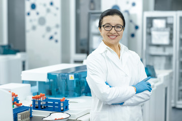 Cheerful senior female scientist posing proudly at her lab