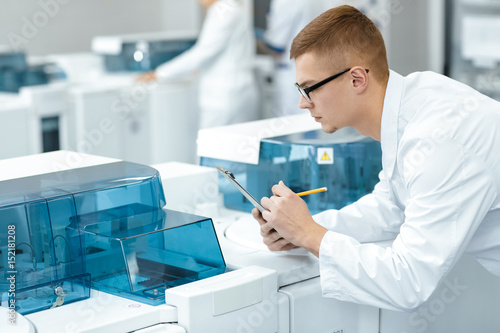 Fotomural  Young scientist watching laboratory machine during an experiment