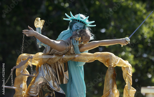 people portraying lady liberty and lady justice kiss during the utah
