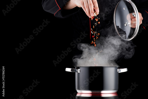 Foto op Plexiglas Koken Modern chef in professional uniform adding spice to steaming pot