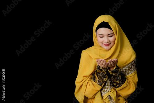 Zdjęcie XXL religijna młoda kobieta muzułmańska modląc się na czarnym tle.