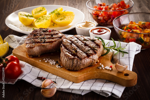Grilled beefsteaks on cutting board on wooden table - dinner preparation
