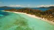 Aerial view of tropical beach on the island Malcapuya, Palawan, Philippines. Beautiful tropical island with sand beach, palm trees. Tropical landscape: beach with palm trees. Seascape: Ocean, sky, sea