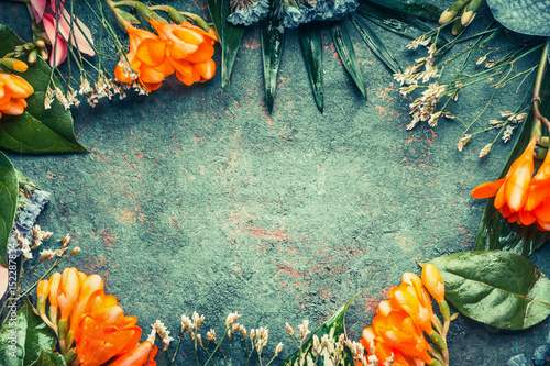Foto op Canvas Bloemen Creative floral frame composing with tropical plant flowers and leaves on dark vintage background, top view