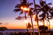 canvas print picture Hawaii sunset with fire torches. Hawaiian icon, lights burning at dusk at beach resort or restaurants for outdoor lighting and decoration, cozy atmosphere.