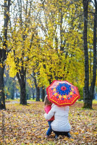 Fotografie, Obraz  Mother and daughter under an umbrella in autumn park
