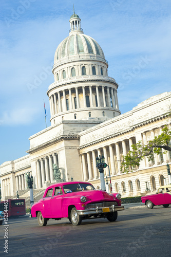 Foto op Aluminium Havana Brightly colored classic American cars serving as taxis pass on the main street in front of the Capitolio building in Central Havana, Cuba