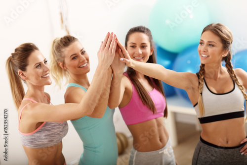 Fototapeten Tanzschule Young women group gicing high five at the gym after workout