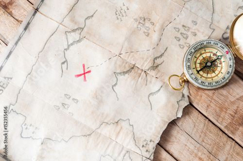 In de dag Wereldkaart Top view to vintage fake treasure map with red cross and compass on wooden desk