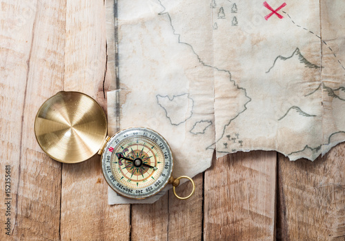In de dag Wereldkaart Compass on wooden desk with fake pirates treasure old map with red mark cross