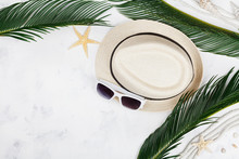 Straw Hat, Sunglasses, Palm Leaves, Rope, Seashell And Starfish On White Table Top View In Flat Lay Style. Summer Holidays, Travel And Vacation Background.