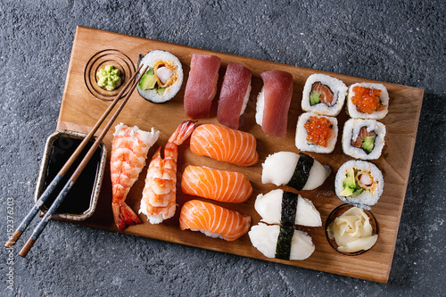 Poster de jardin Sushi bar Sushi Set nigiri and sushi rolls on wooden serving board with soy sauce and chopsticks over black stone texture background. Top view with space. Japan menu