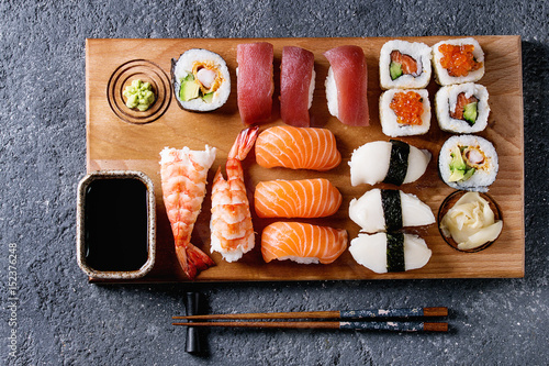 Foto op Aluminium Sushi bar Sushi Set nigiri and sushi rolls on wooden serving board with soy sauce and chopsticks over black stone texture background. Top view with space. Japan menu
