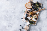 Fototapeta Dmuchawce - Berries blackberry and blueberry, honey on dipper, rosemary, sliced goat cheese with bread served on wooden board over gray texture background. Summer sandwich. Top view with space
