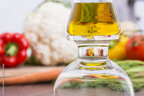 Foto auf AluDibond Küche Olive oil bottle with magnification of vegetables in the background
