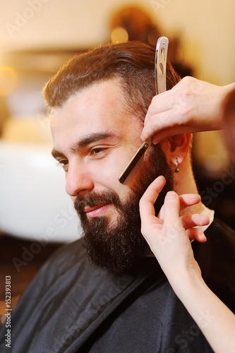 Beautiful manly bearded man in a barbershop on a beard styling