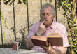 Mature man sitting outside reading a book on a sunny day