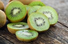 Sliced Kiwi Fruit On Wooden Ba...