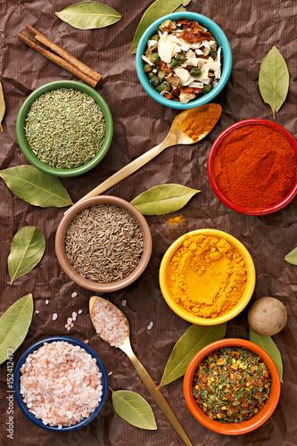 przyprawy-w-kolorowe-miski-ogladane-z-gory-rozne-przyprawy-na-ciemnym-tle-wloska-mieszanka-kminek-papryka-chili-curry-w-proszku-sol-himalajska-pieprz-czosnek-cynamon-suszony-pomidor-widok-z-gory