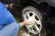 Mężczyzna myje gąbką z szamponem samochodowym felgę aluminiową.