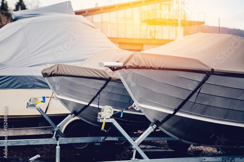 Fotografia  Row of boats in storage for the winter under the awning