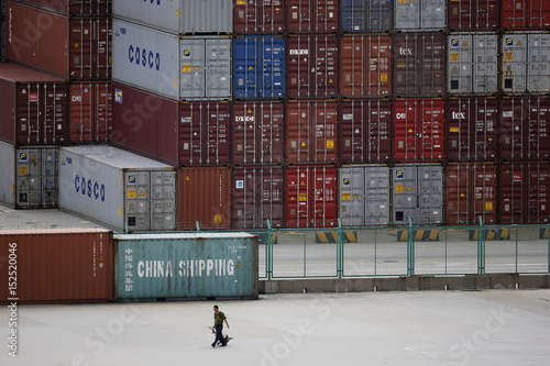 A man walks past a container area at the Yangshan Deep Water