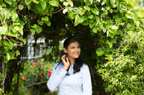 Photo  Closeup portrait of confident smiling happy pretty young woman in blue shirt enjoying a fresh new day, isolated background of green shrubs and flowers