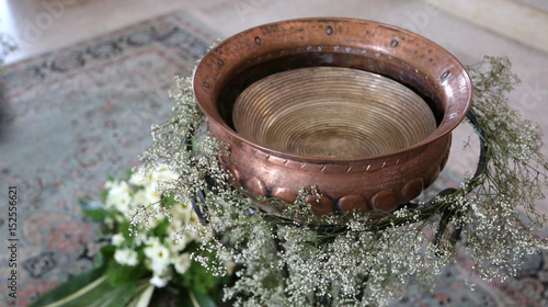 Slika na platnu Ancient Small baptismal font in copper decorated with flowers du