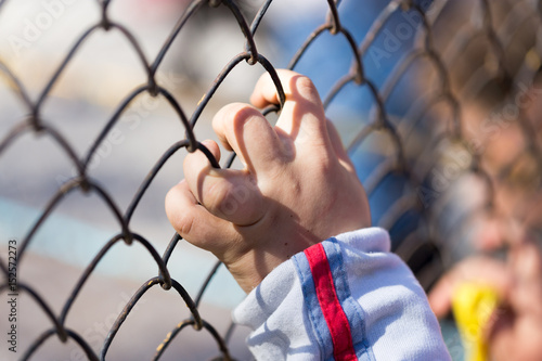 Fotomural Child's hand on a grid of a metal fence