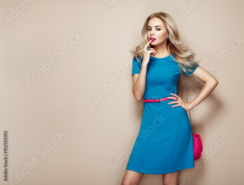 Blonde young woman in elegant blue summer dress Wall mural