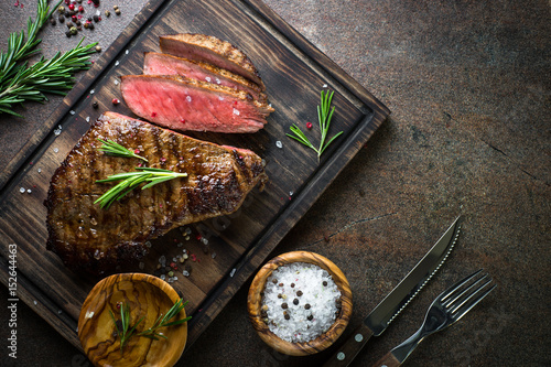 Poster Steakhouse Grilled beef steak on wooden board. Top view copy space.