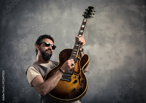 Photo  adult caucasian guitarist portrait playing electric guitar on grunge background