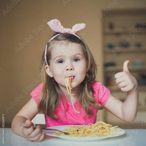 cute girl eating pasta and thumb