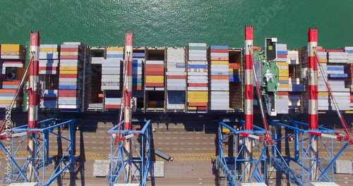 Plakat Port handlowy ze statkiem kontenerowym podczas załadunku i rozładunku - widok z góry na dół.