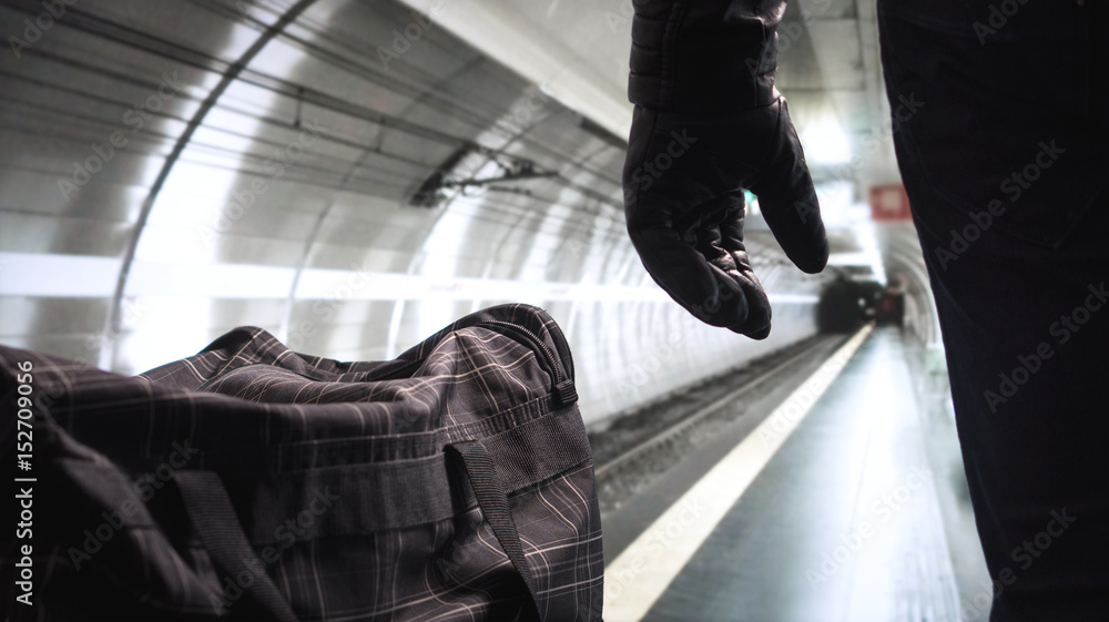 Fototapeta Bomber standing next to his black bomb bag planning a strike. Terrorist in underground subway tunnel looking at the empty metro platform. Security threat in public transportation. Terrorism concept.