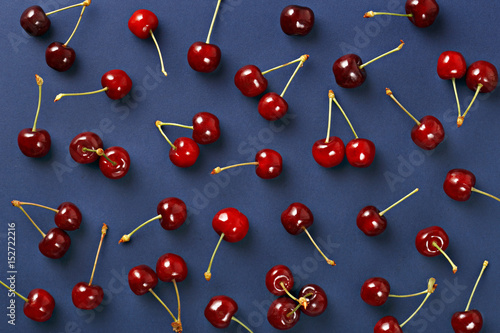 Cherry pattern. Flat lay of cherries on a dark blue background.Top view