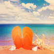 pair of orange flip flop sandals in sand on the beach near sea water, retro toned