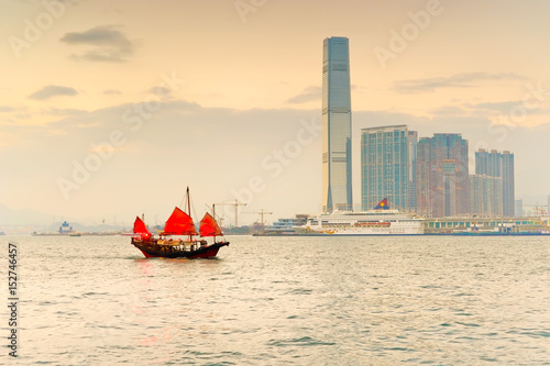 Photo  Hong Kong skyline with a red Chinese sailboat passing on the Victoria Harbor at