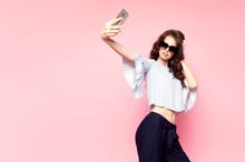 Studio Shot Of Beautiful Woman Taking Selfie At Pink Wall.