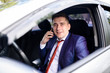 A businessman talks on the phone in the car