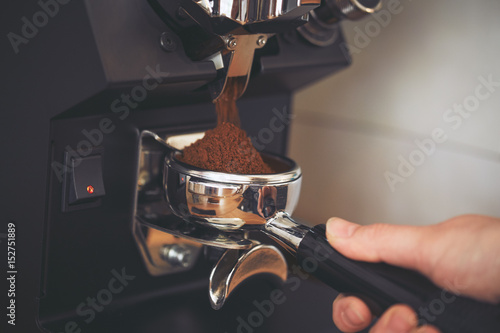 Canvas Print Coffee grinder grinds freshly coffee beans in a portafilter